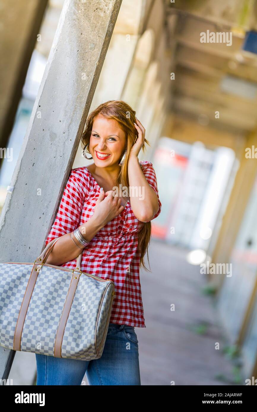 Standing leaning inclined on concrete post hand touching touch hair head giggling loudly squinting eyes Stock Photo
