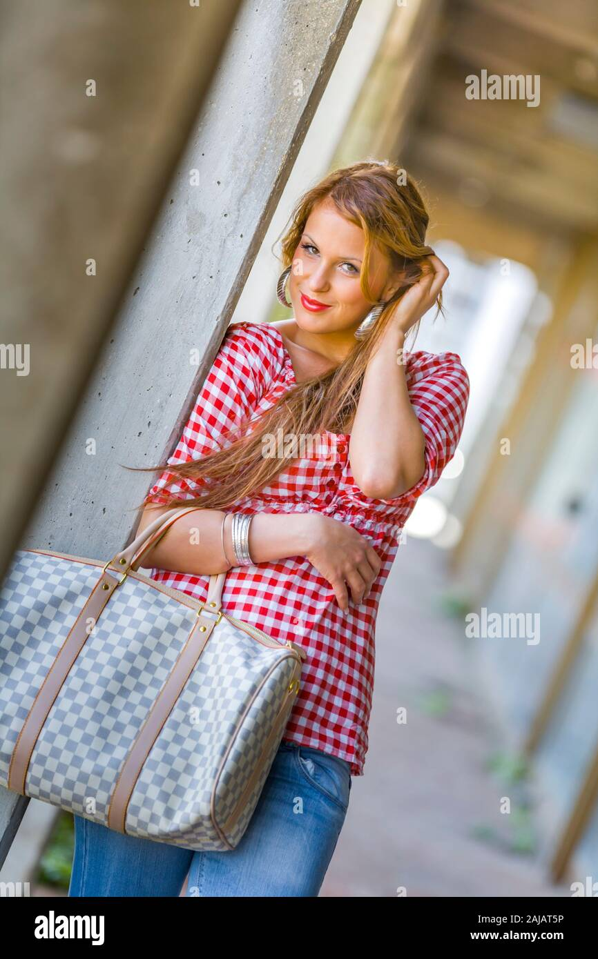 Standing leaning inclined on concrete post hand touching touch hair head with slight smile Stock Photo
