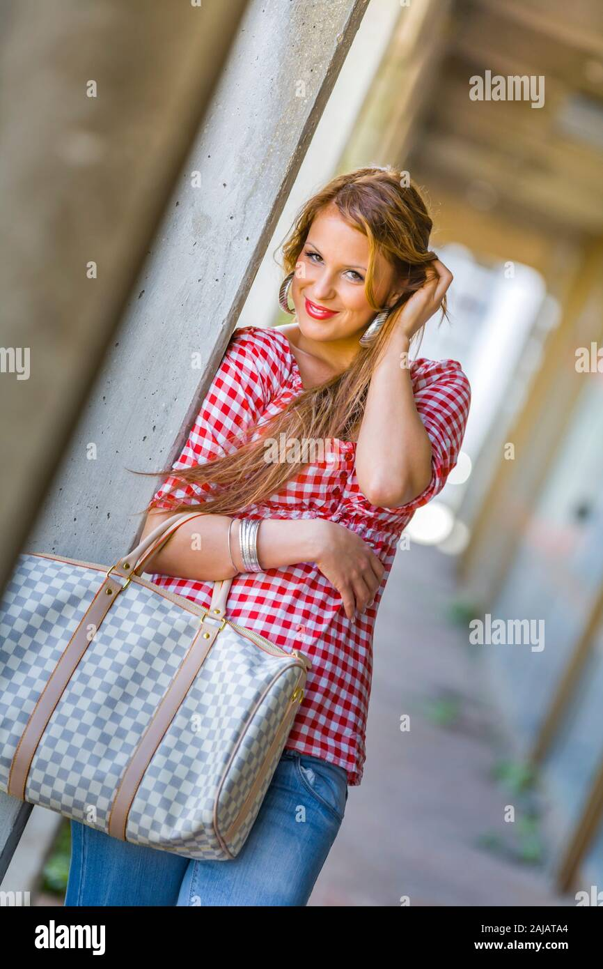 Standing leaning inclined on concrete post hand touching touch hair head smile smiling Stock Photo