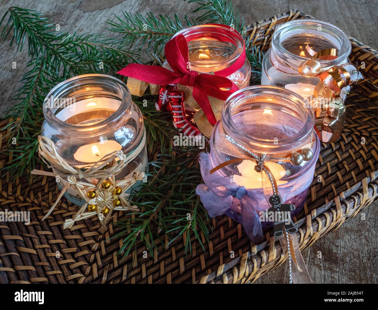 Several tea candles burning in decorated glasses on Christmas Stock Photo