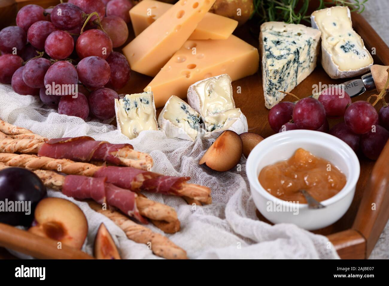 Antipasto. Dish with crispy grissini wrapped in sun-dried bacon, slices of brie cheese, camembert, blue cheese, radamer and muscat grape vine with fru Stock Photo