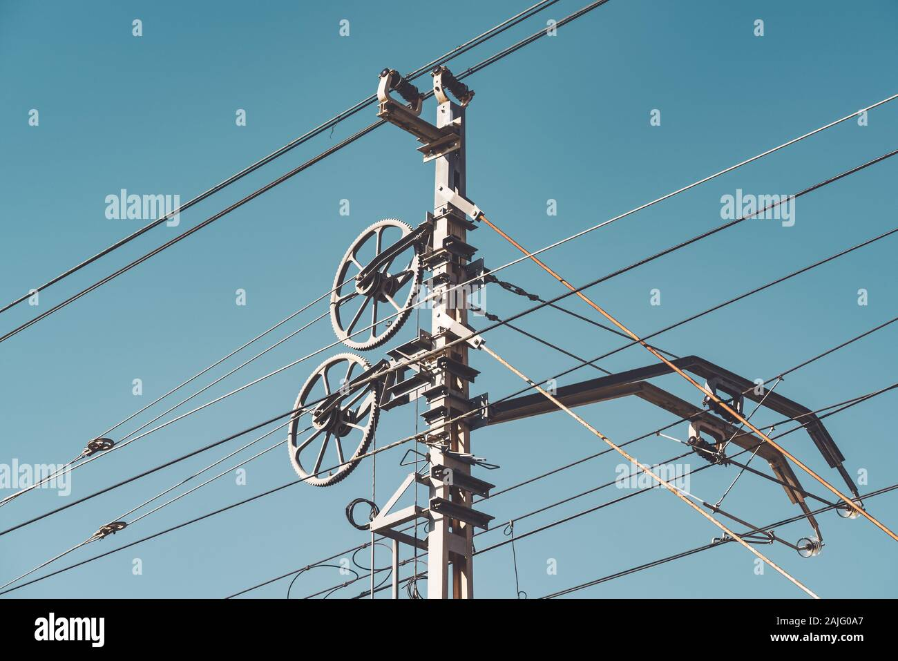 Railway catenary system and poles against clear blue sky. Stock Photo