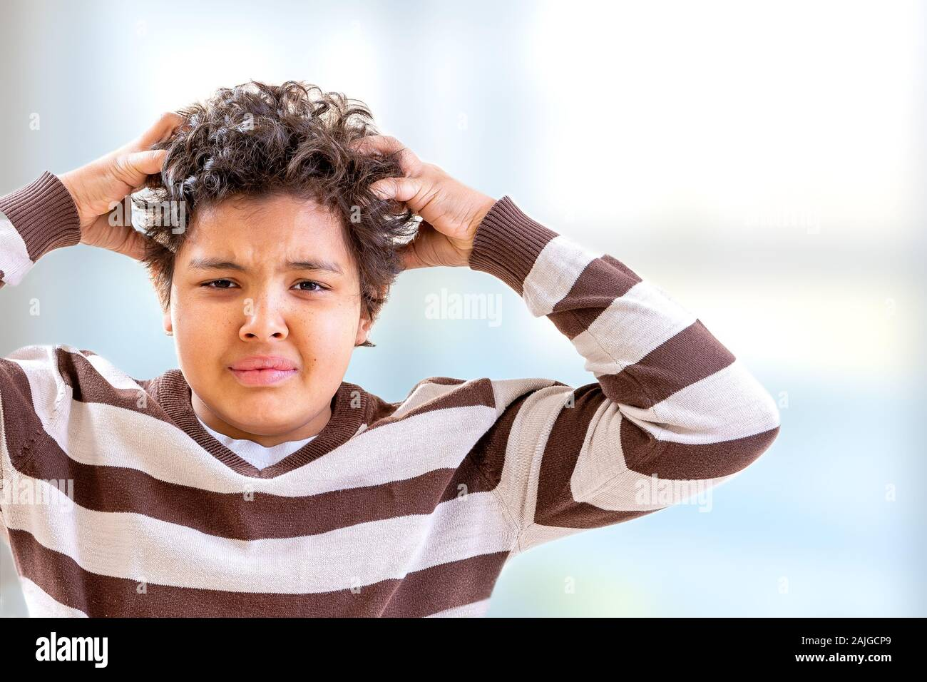 Stress boy scratching his hair with confused expression Stock Photo