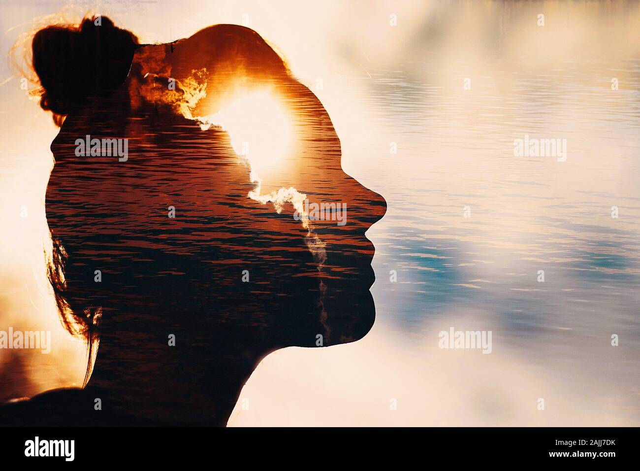 Sun peeks out from behind the clouds in woman's head. Stock Photo
