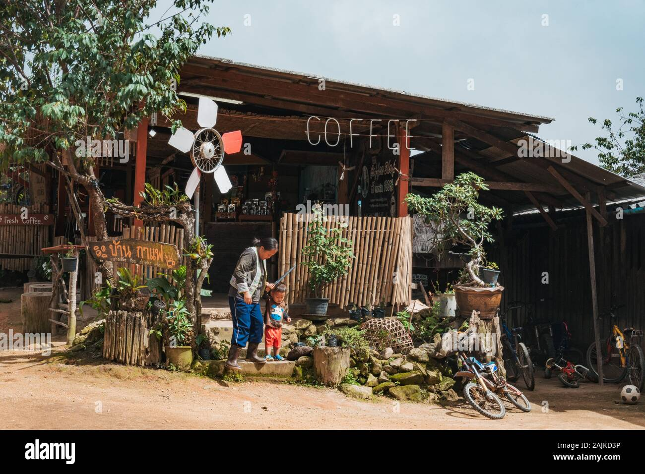 A Thai woman helps a young boy down stairs at a quiet, small wooden coffee shop in a rural village atop of a hill outside of Chiang Mai, Thailand Stock Photo