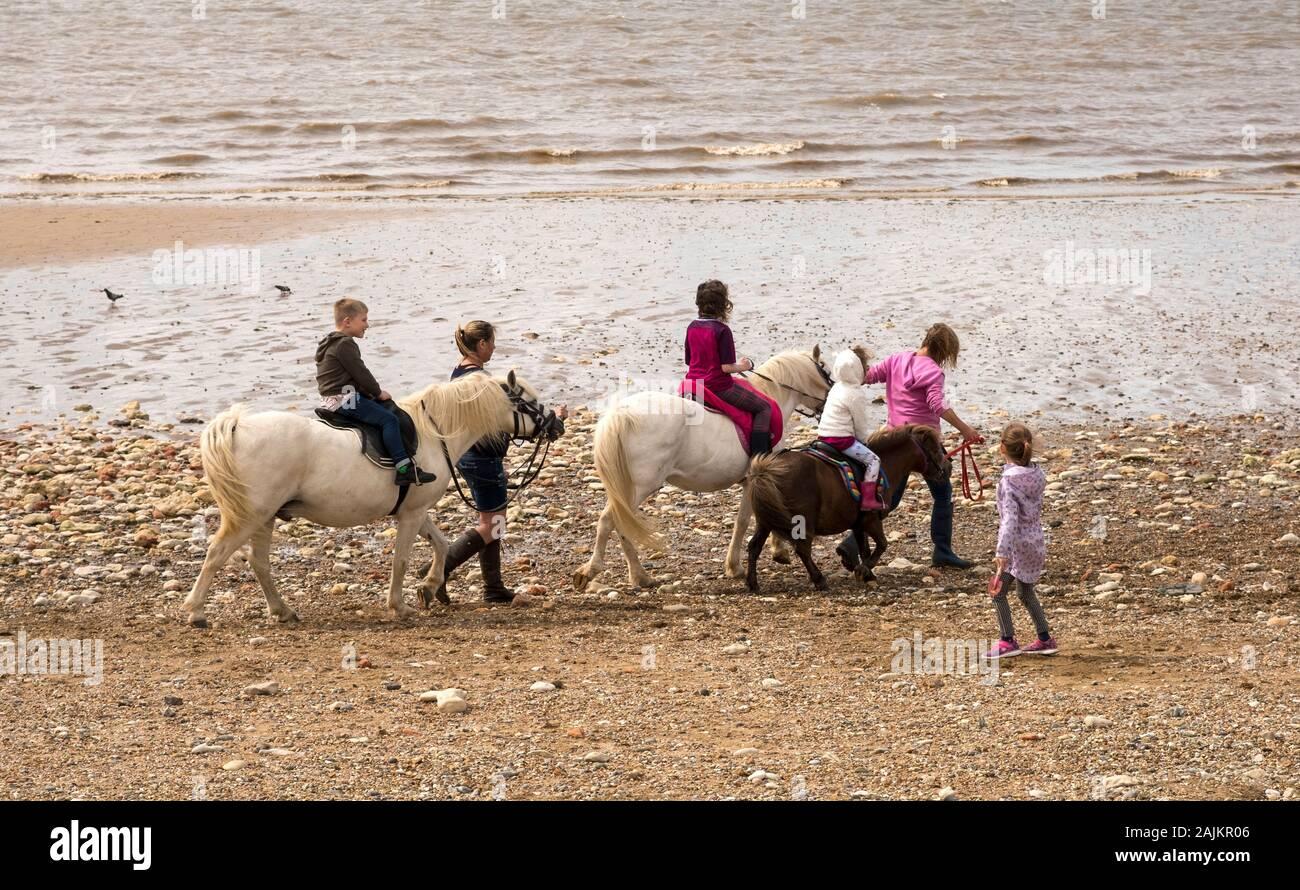 Children having a donkey ride on the beach in Hunstanton, North Norfolk, UK Stock Photo