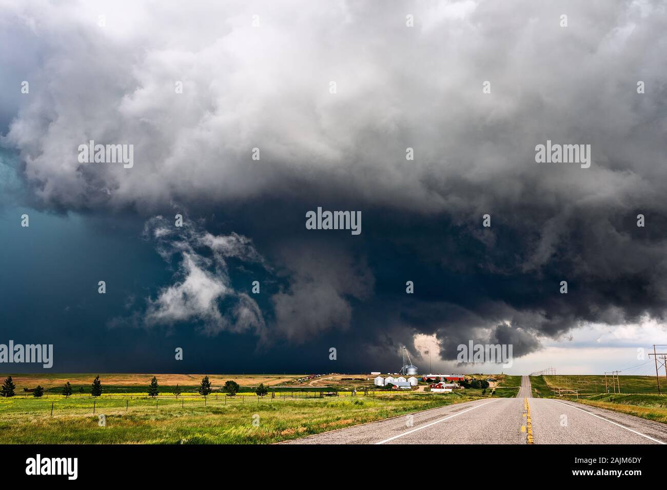 A stormy sky with dramatic, dark clouds sweeps across a farm as a severe thunderstorm approaches Anton, Colorado. Stock Photo