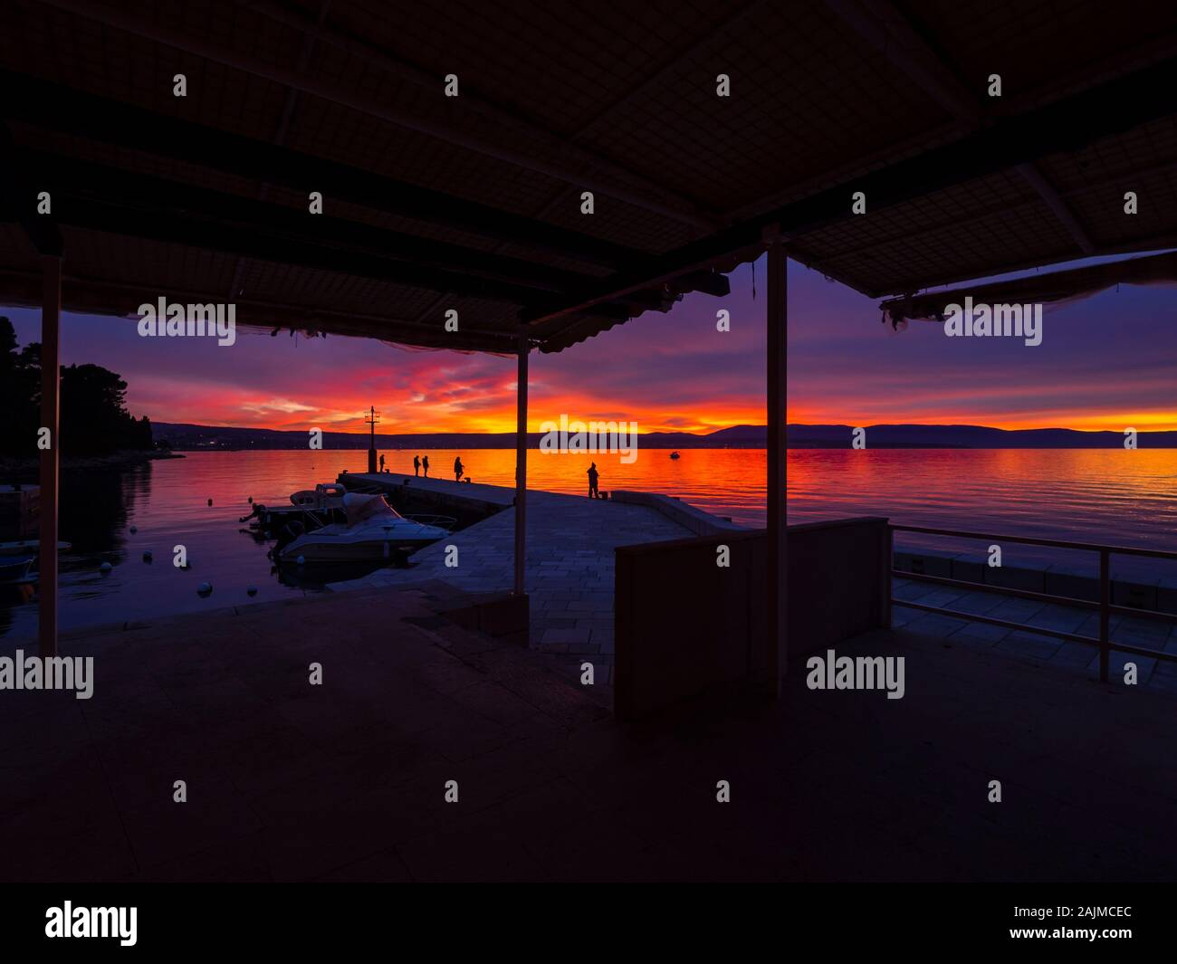 Fishermen before sunset scenery in small harbor in Malinska in Croatia framed by house roof Stock Photo