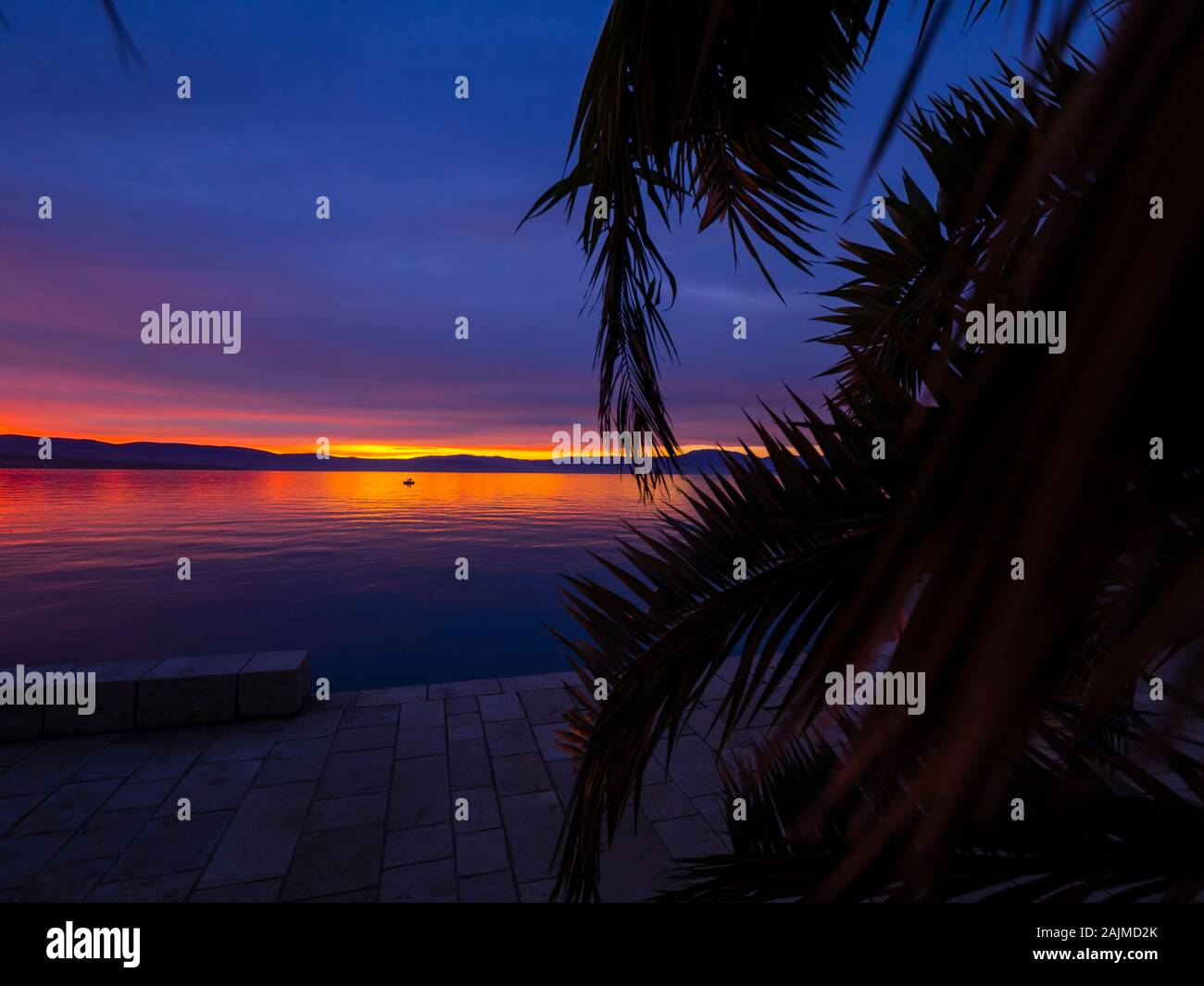 Sunset in small harbor in Malinska in Croatia single tiny small boat in distance Stock Photo