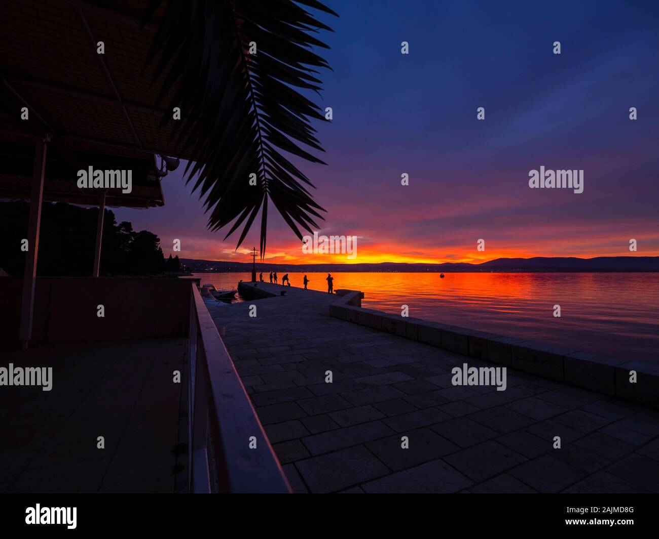 Fishermen on seawall before sunset scenery in small harbor in Malinska in Croatia Stock Photo