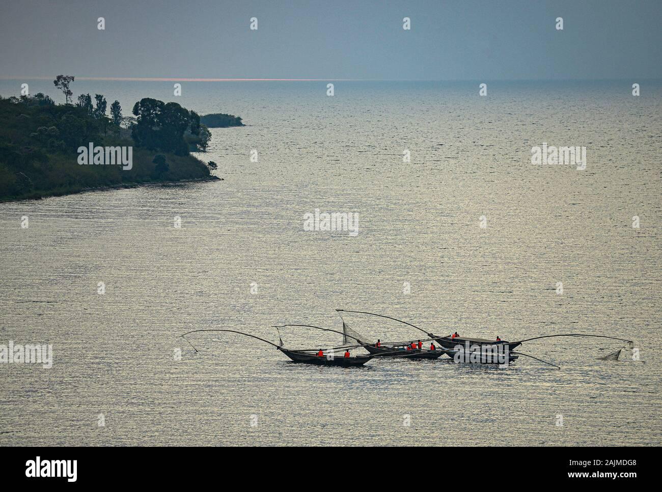 Fishing Canoes on the Lake with the Sun's Reflection on Water. Lake Kivu, Rwanda. Lake Kivu is shared by Rwanda and the Democratic Republic of Congo. Stock Photo
