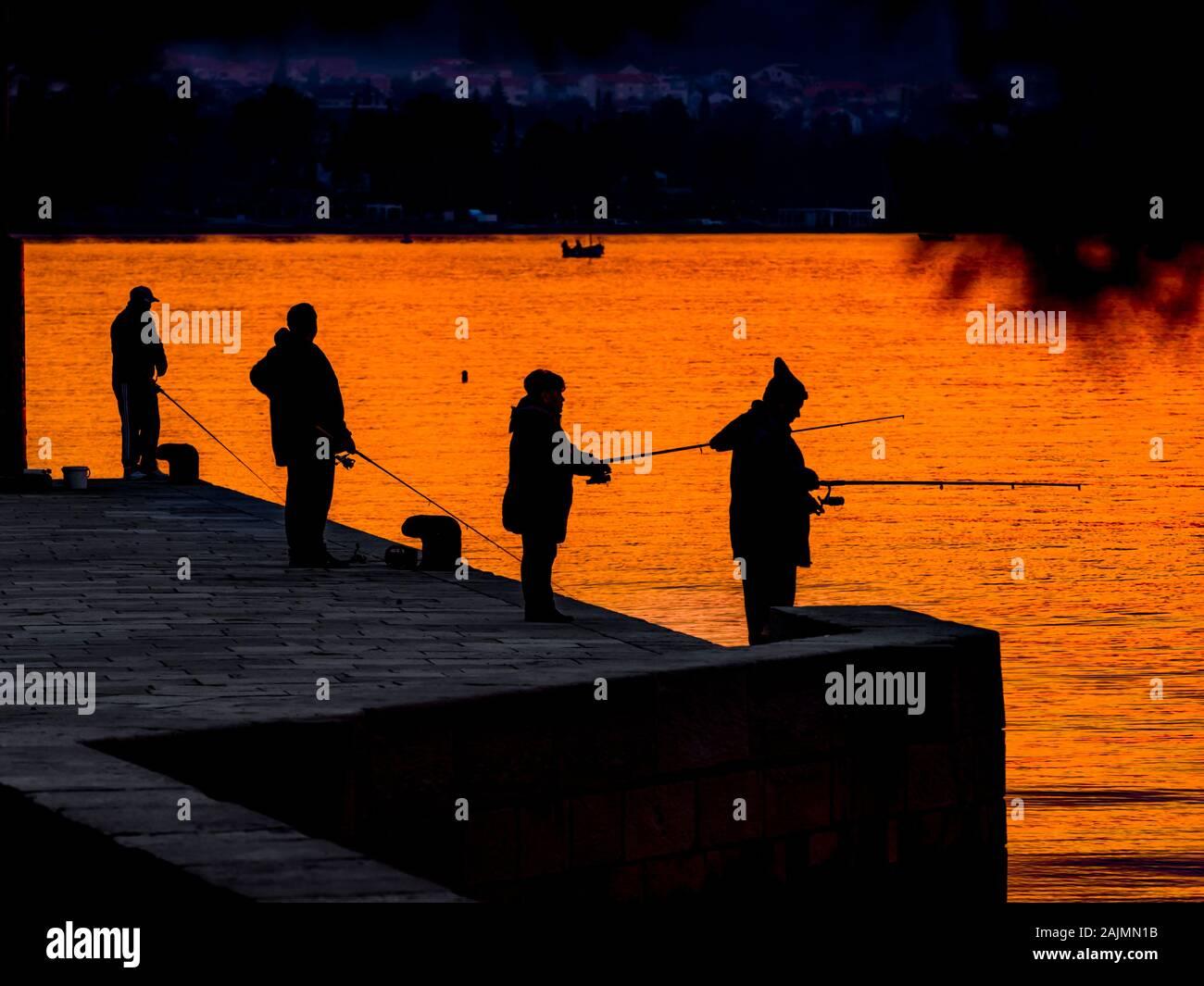 Fishermen silhouette silhouettes silhouetting before sunset in small harbor in Malinska in Croatia Stock Photo