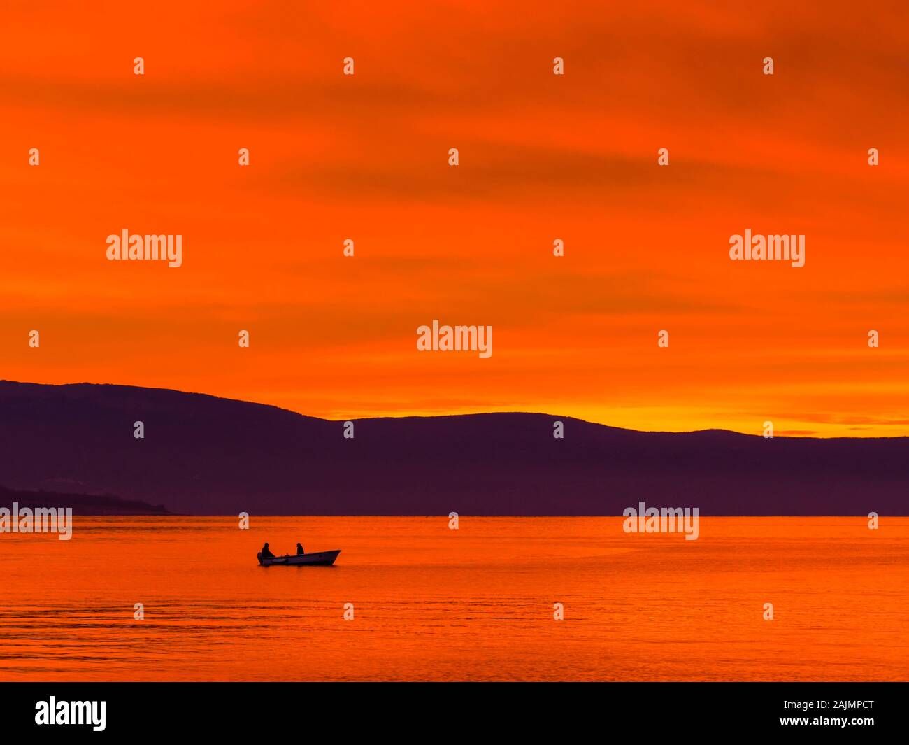 Lonely boat with two fishermen before glorious sunset sea scenery Stock Photo