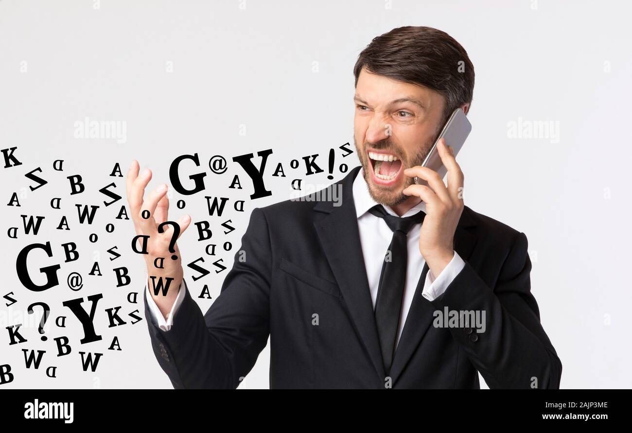 Phone Rage. Furious Businessman Shouting While Talking On Cellphone, Diverse Alphabet Letters Coming Out Of His Mouth, Light Studio Background Stock Photo