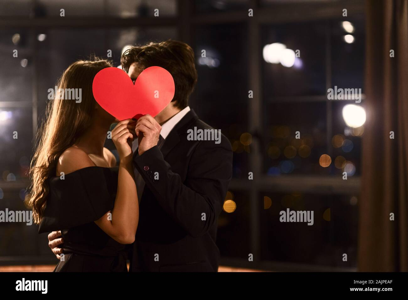 Download Cute Couple In Love Kissing Behind A Paper Heart Celebrating Saint Valentine S Day Concept Copy Space Stock Photo Alamy