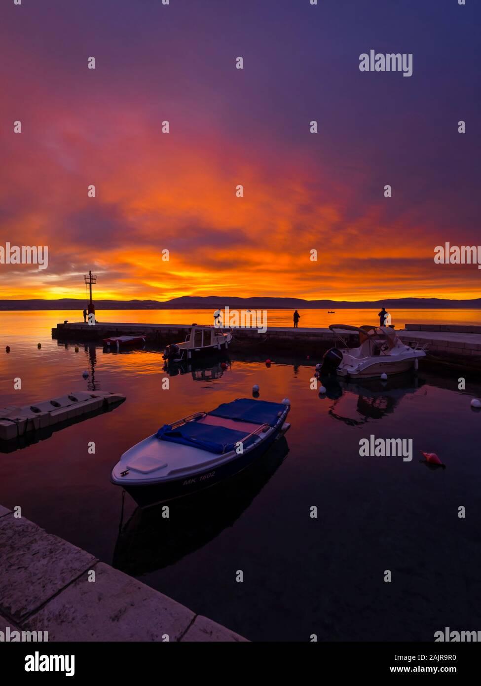 Fishermen before sunset scenery in small harbor in Malinska in Croatia glorious sky peaceful atmospheric seawall Ribarsko selo Haludovo Kvarner Stock Photo