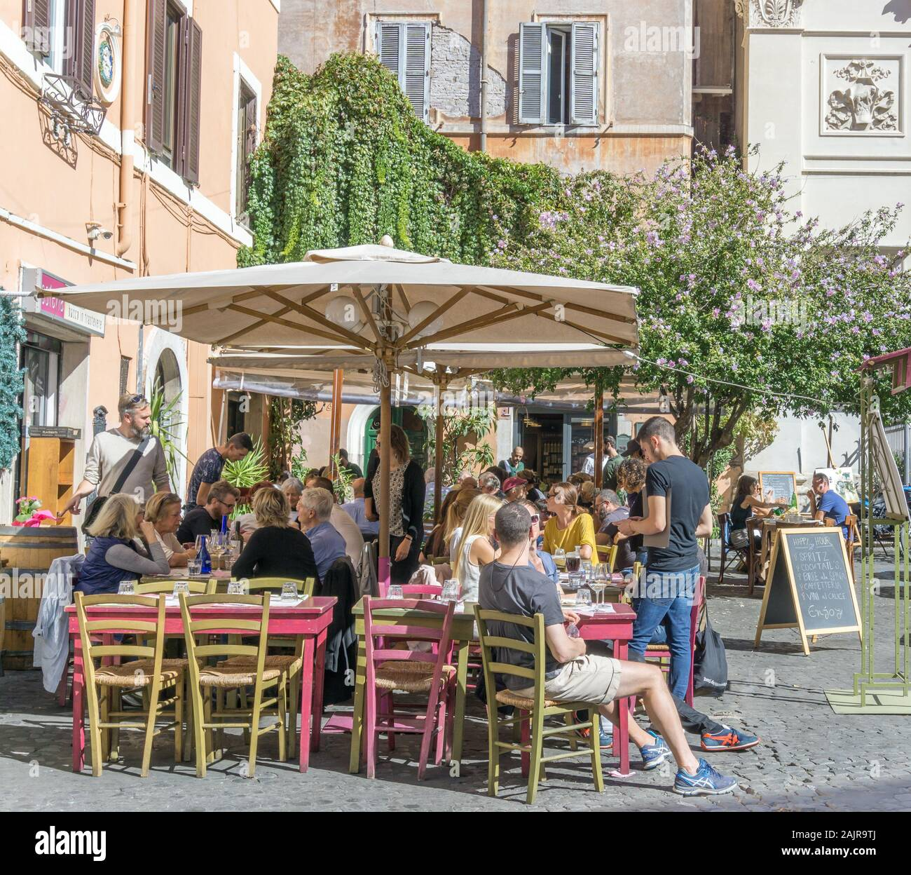 ROME, ITALY - OCTOBER 10, 2017: people are eating outdoors in a typical trattoria in Trastevere, historic district of Rome, Italy Stock Photo