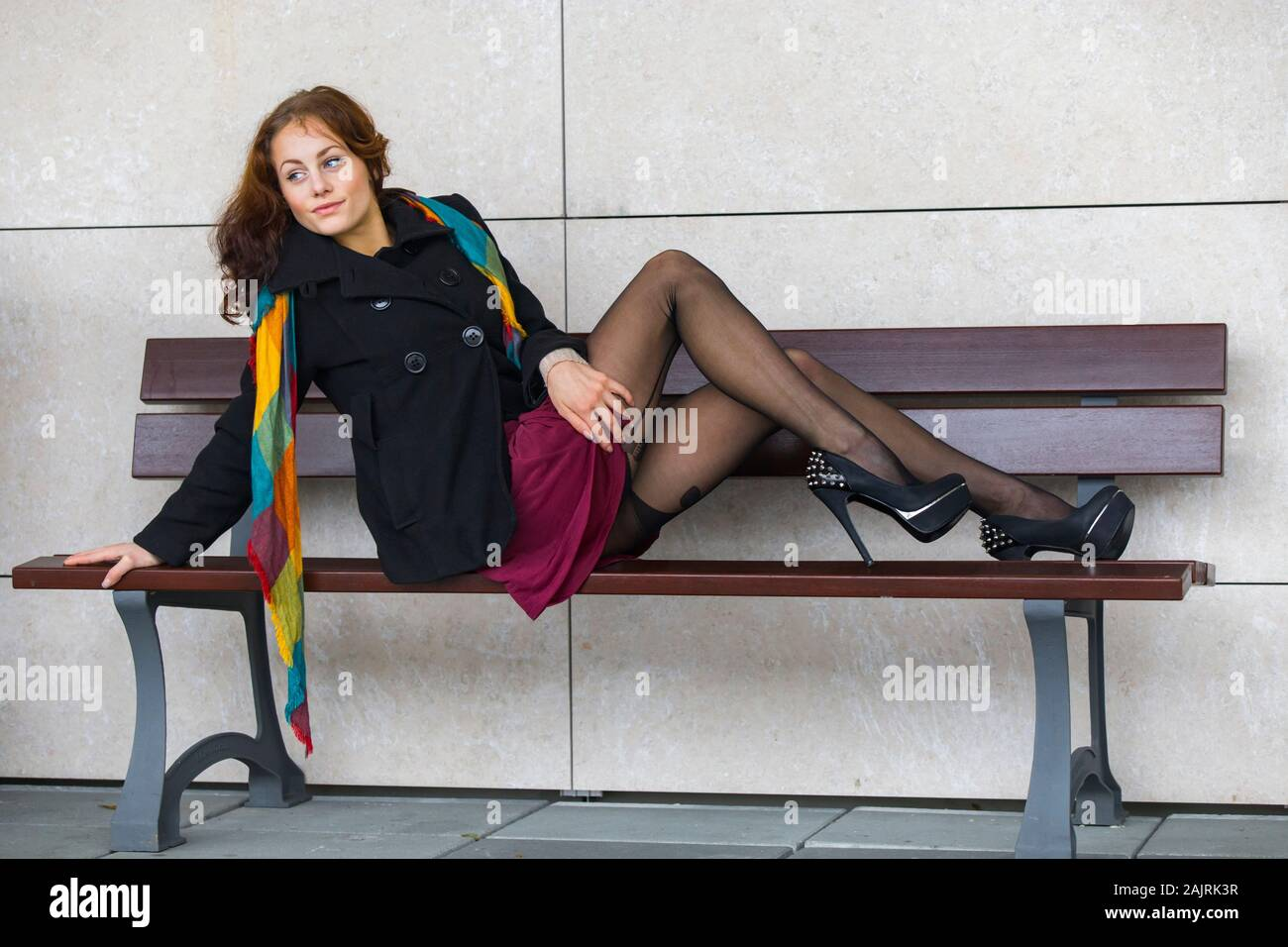 Sitting on wooden bench wearing sexy legware looking away aside sideview side-view provocation alluring sexual allurement lure luring Stock Photo