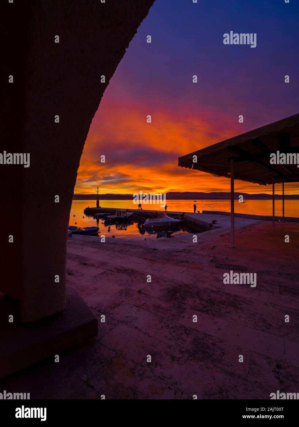 Fishermen standing on edge before sunset scenery in small peaceful harbor in Malinska in Croatia Stock Photo