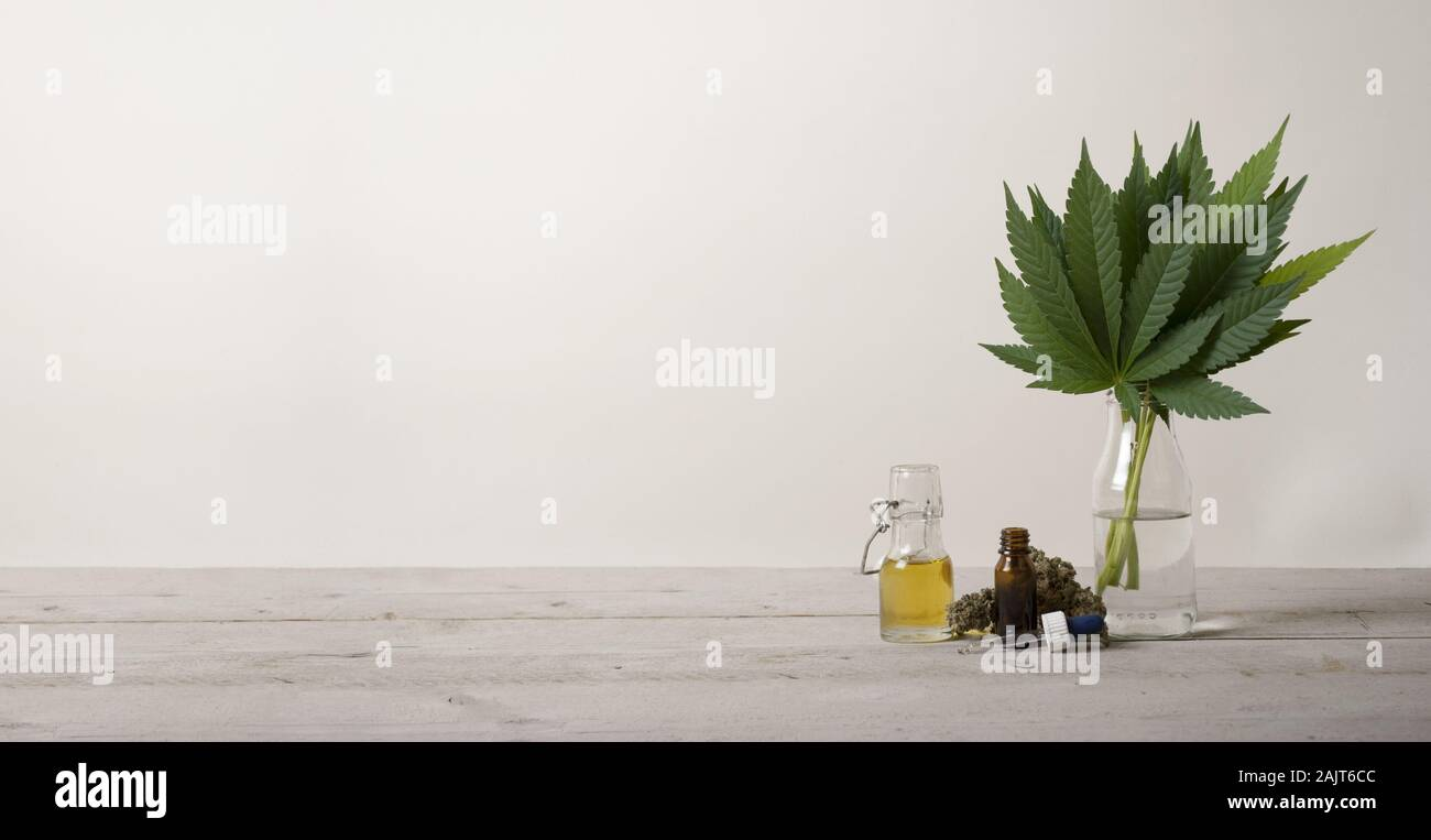banner showing CBD oil in glass bottle, Cannabis sativa marijuana weed leaves and dropper bottle, on industrial wooden ground floor Stock Photo