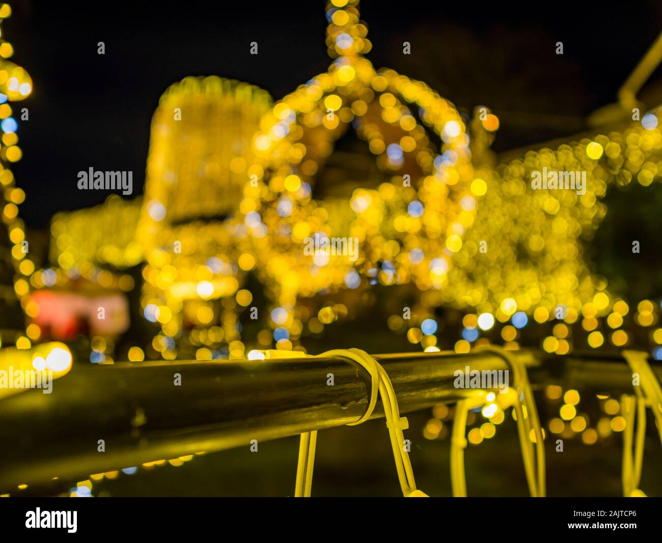 Festive crown defocused blurry bokeh in background illumination Trsat fort in Rijeka Croatia isolated metal fence in foreground Stock Photo