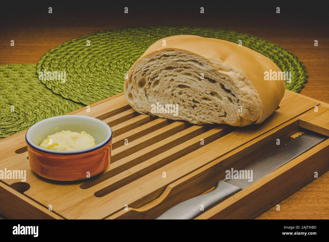 Cutted big bread at the table with knife and butter and placemats Stock Photo