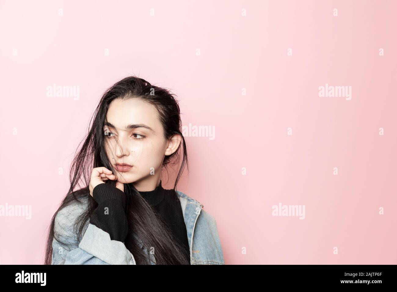 Portrait of happy middle-eastern female posing against a pink background. Studio portrait of a stylish young woman. Beauty, fashion, seasonal vogue Stock Photo