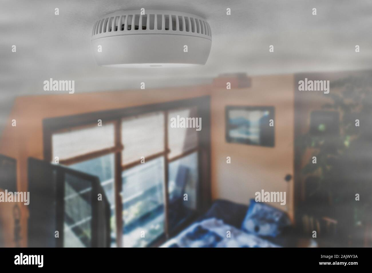 Domestic smoke alarm / battery powered smoke detector on the ceiling in room filled with smoke from fire at home Stock Photo