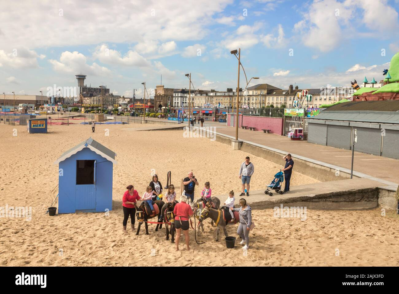 26 June 2019: Great Yarmouth, Norfolk, UK - Children riding donkeys at the beach, with parents assisting. Stock Photo