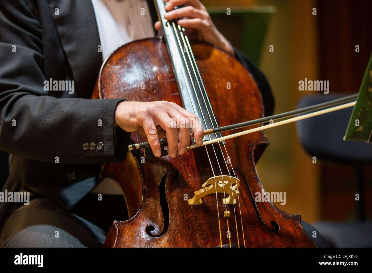 Symphonic orchestra performing on stage and playing a classical music concert, cellist in the foreground Stock Photo
