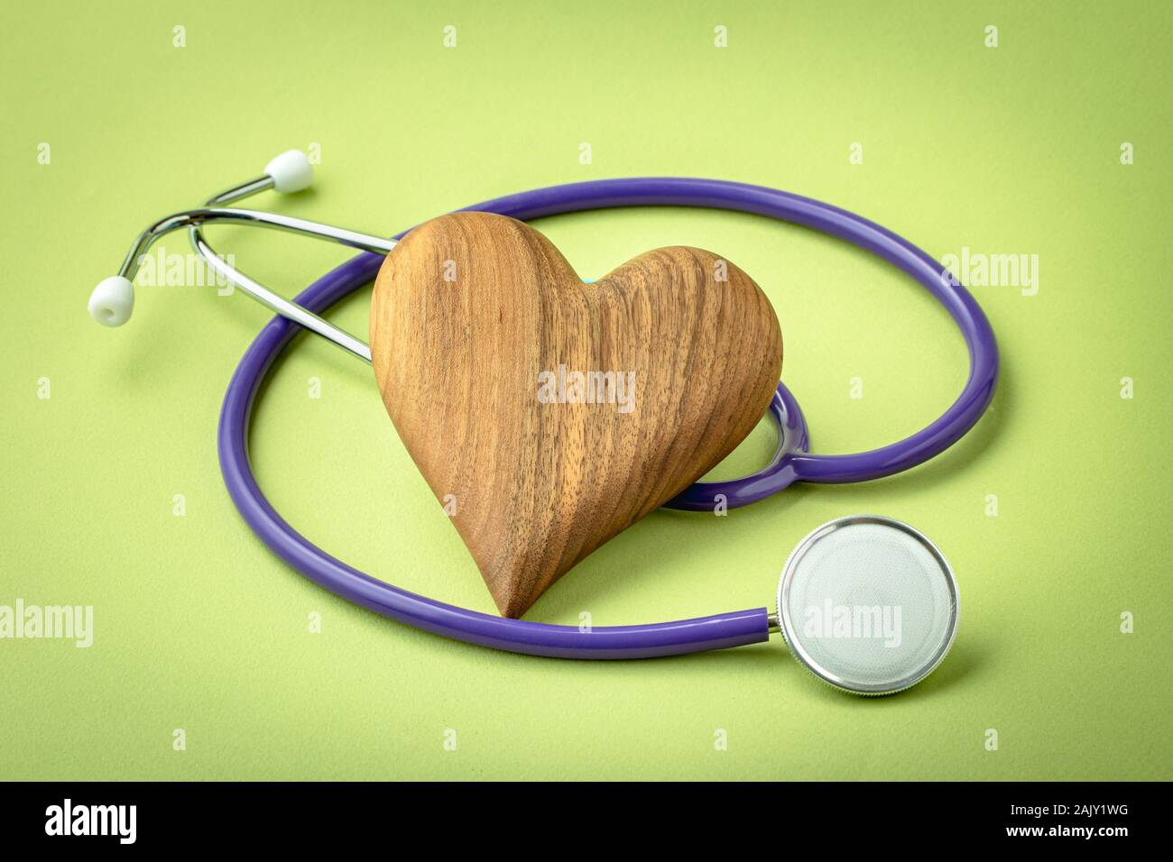 Wooden heart with stethoscope on green background Stock Photo
