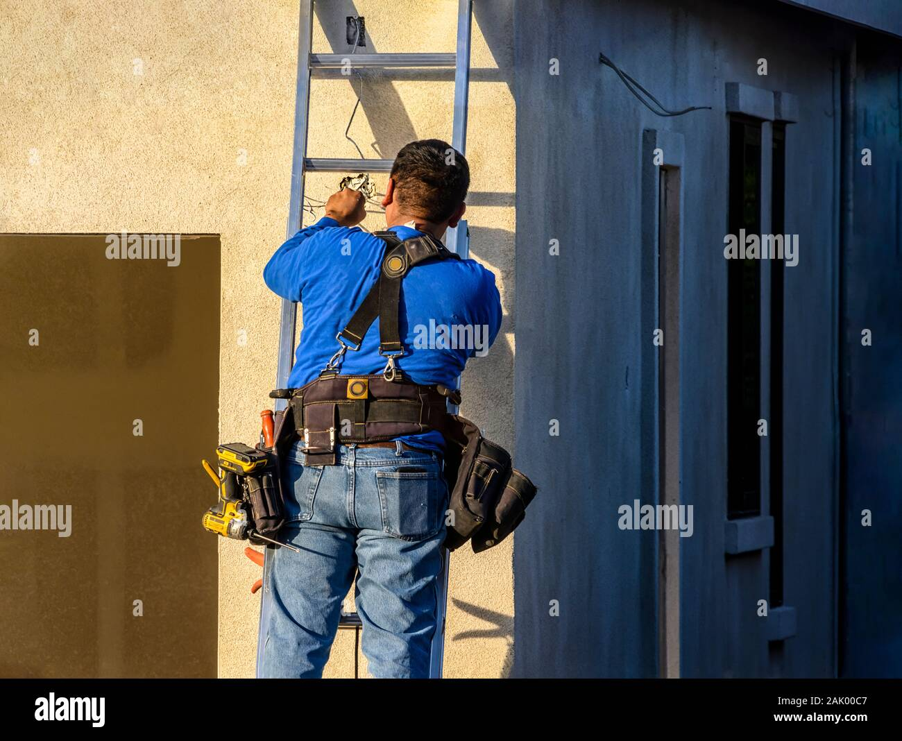 A male electrician wiring an outdoor light fixture on the front of a new house. Space for text Stock Photo