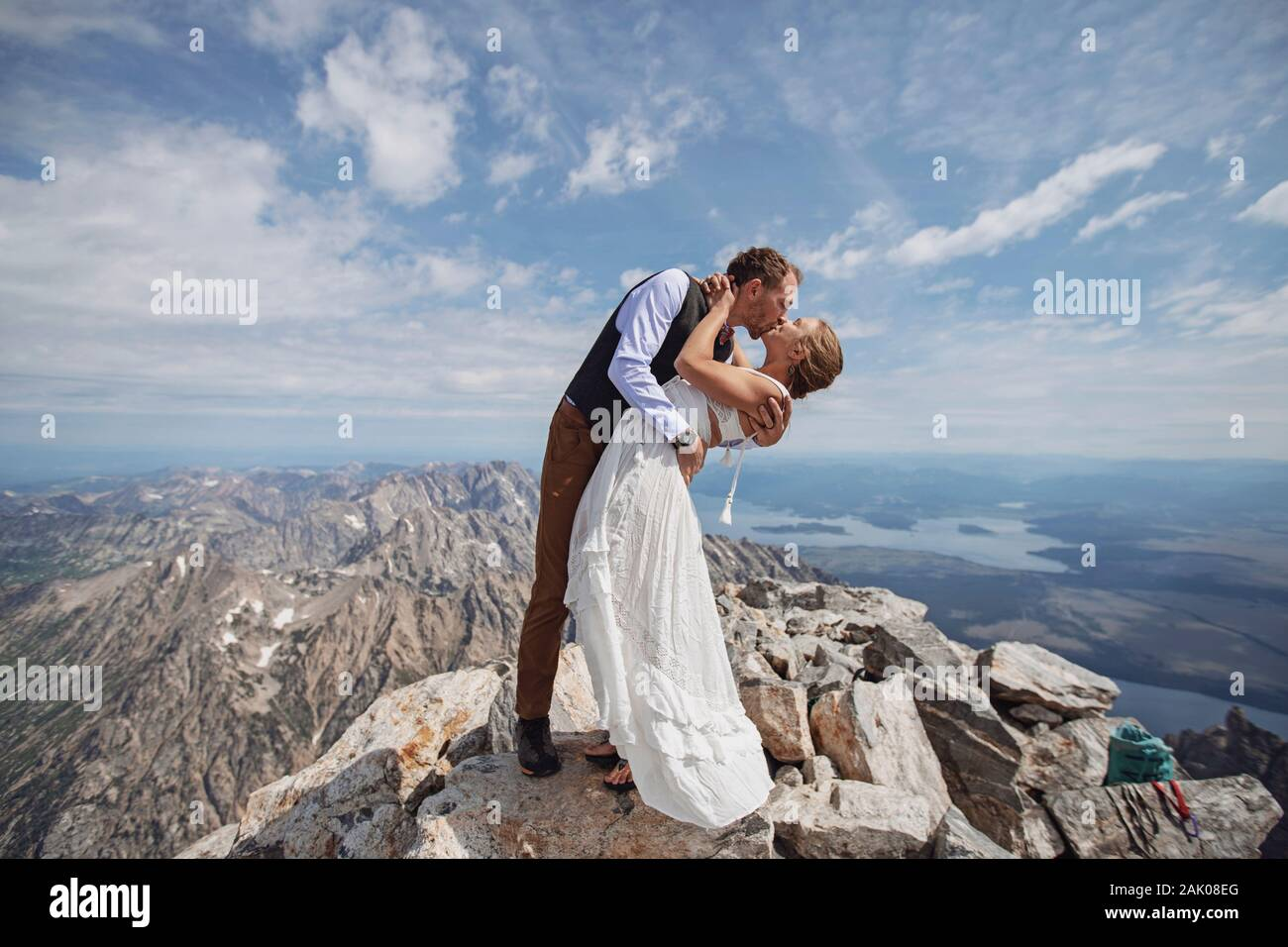 Groom dips bride after getting married on summit of mountain Stock Photo