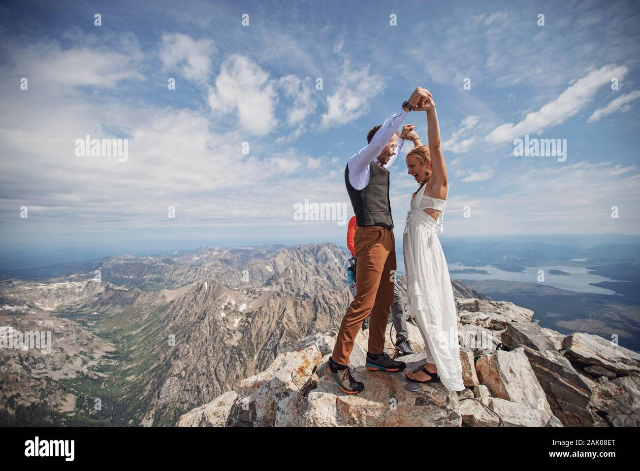 Bride and Groom celebrate after getting married on summit of mountain Stock Photo