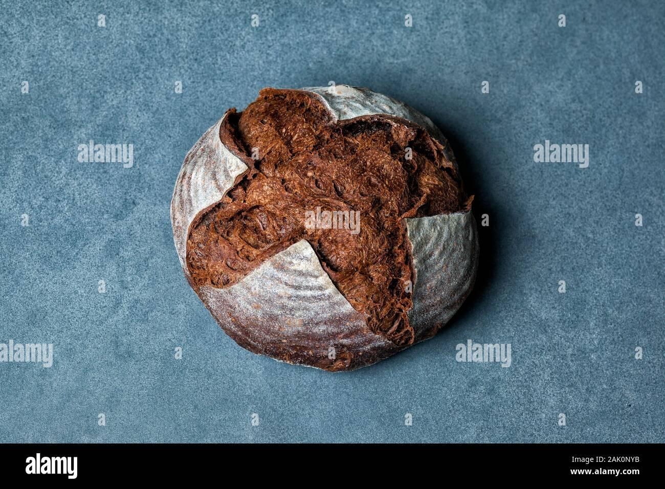 Artisan loaf of traditional Homemade Pumpernickel sourdough Boule bread with crust on a wooden board Stock Photo