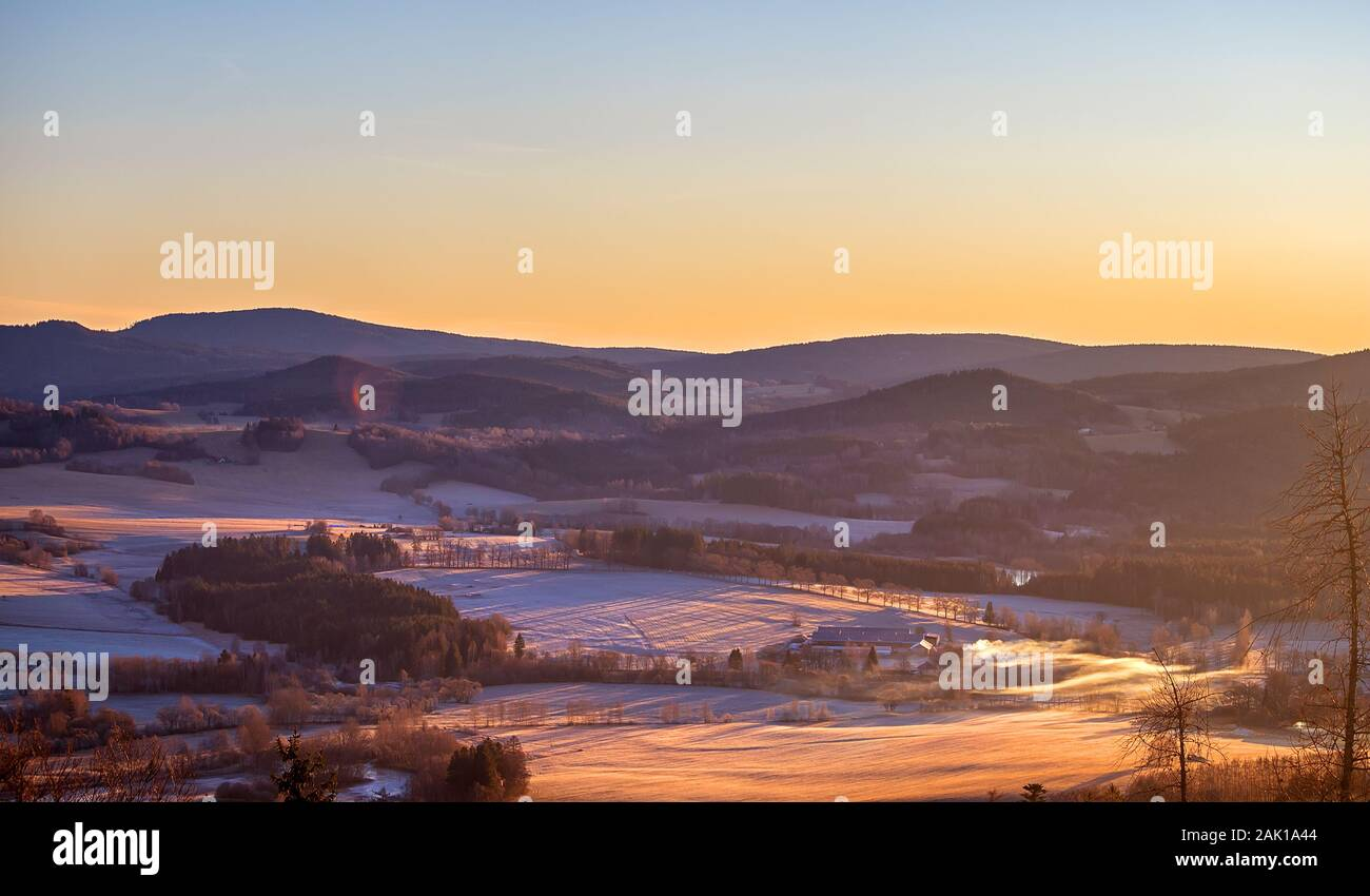 sunrise in the mountains - winter hilly landscape with forests, trees and meadows (with hoarfrost and snow) Stock Photo