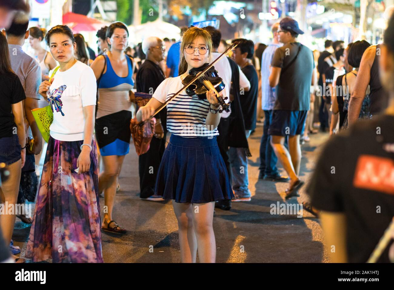 Chiang Mai, Thailand 9 April 2017 : Young woman playing vintage violin in the streets of Chiang Mai in Thailand Stock Photo