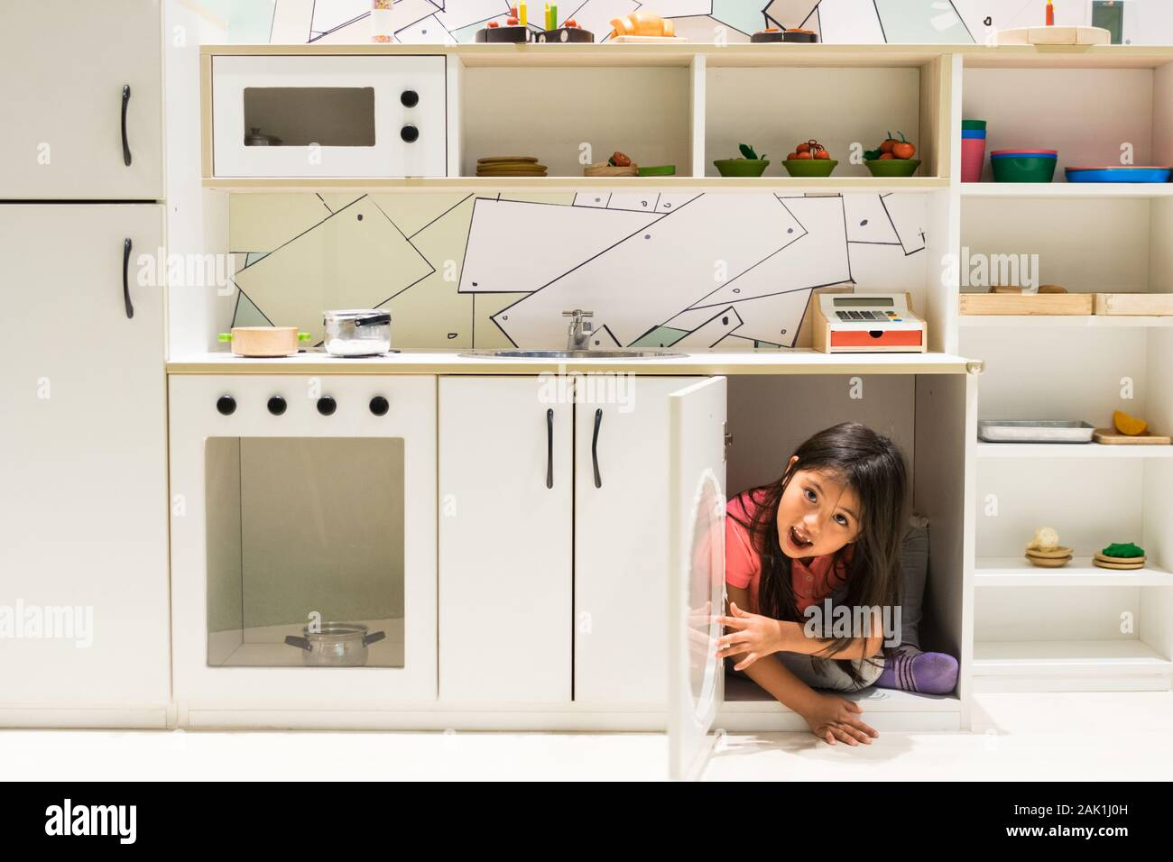 Beautiful girl coming out of the kitchen cupboard for girls Stock Photo