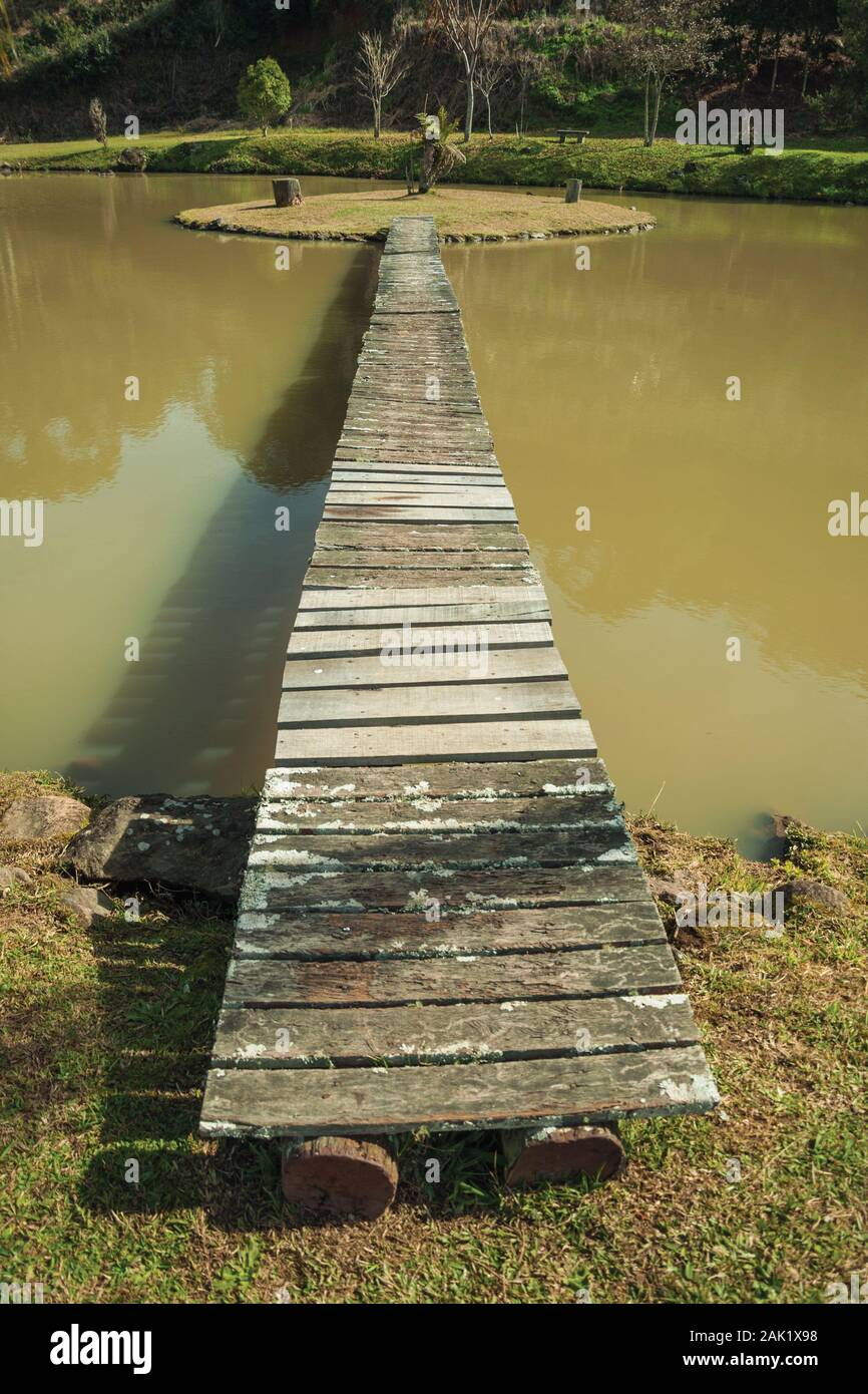 Wooden walkway going to a small island in pond from a garden with palm trees near Bento Goncalves. A wine producing country city in southern Brazil. Stock Photo