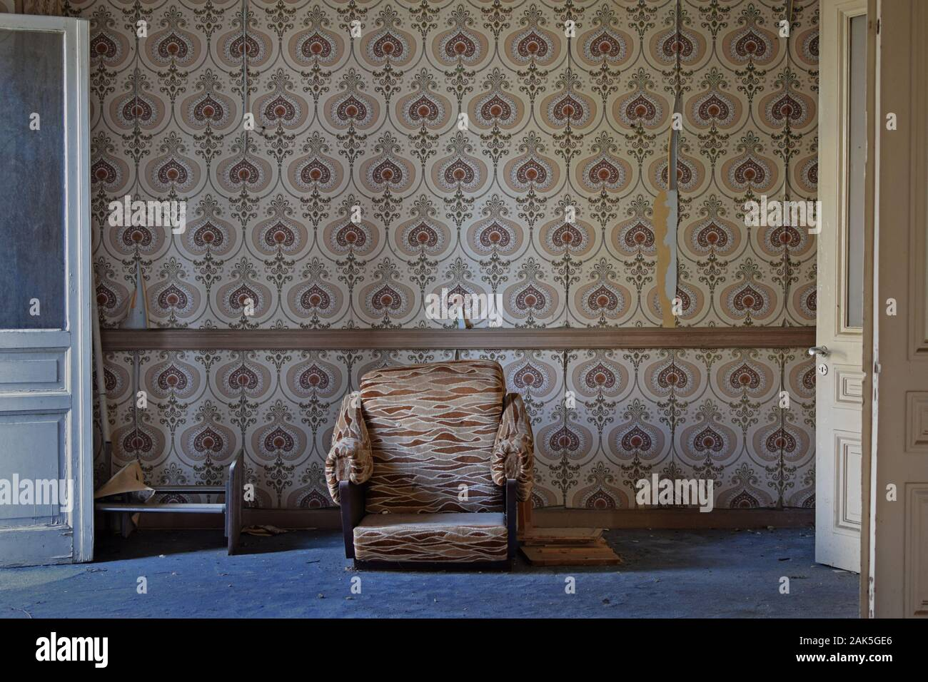 broken armchair and torn retro wallpaper in abandoned house living room 2AK5GE6