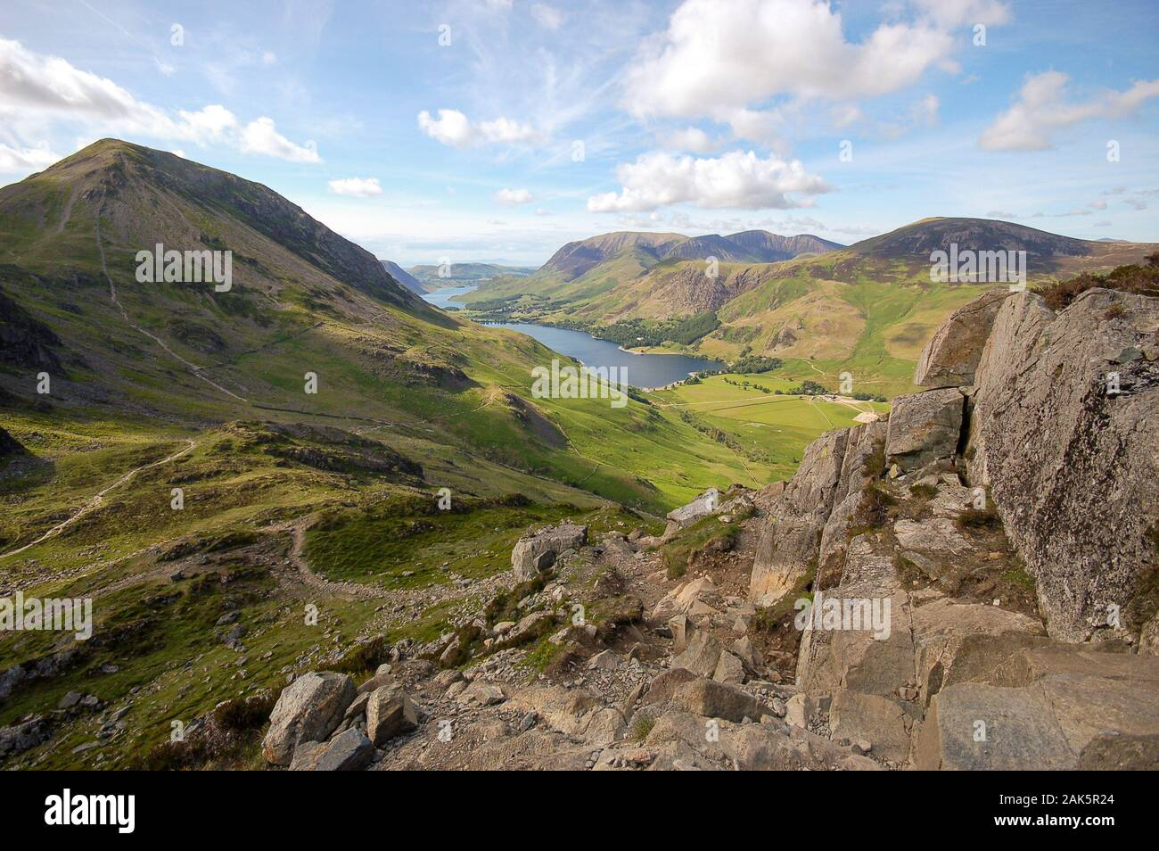 Buttermere village and lake, and Crummock Water, lie in the valley below the mountains of the English Lake District, seen from the peak of Giant Hayst Stock Photo
