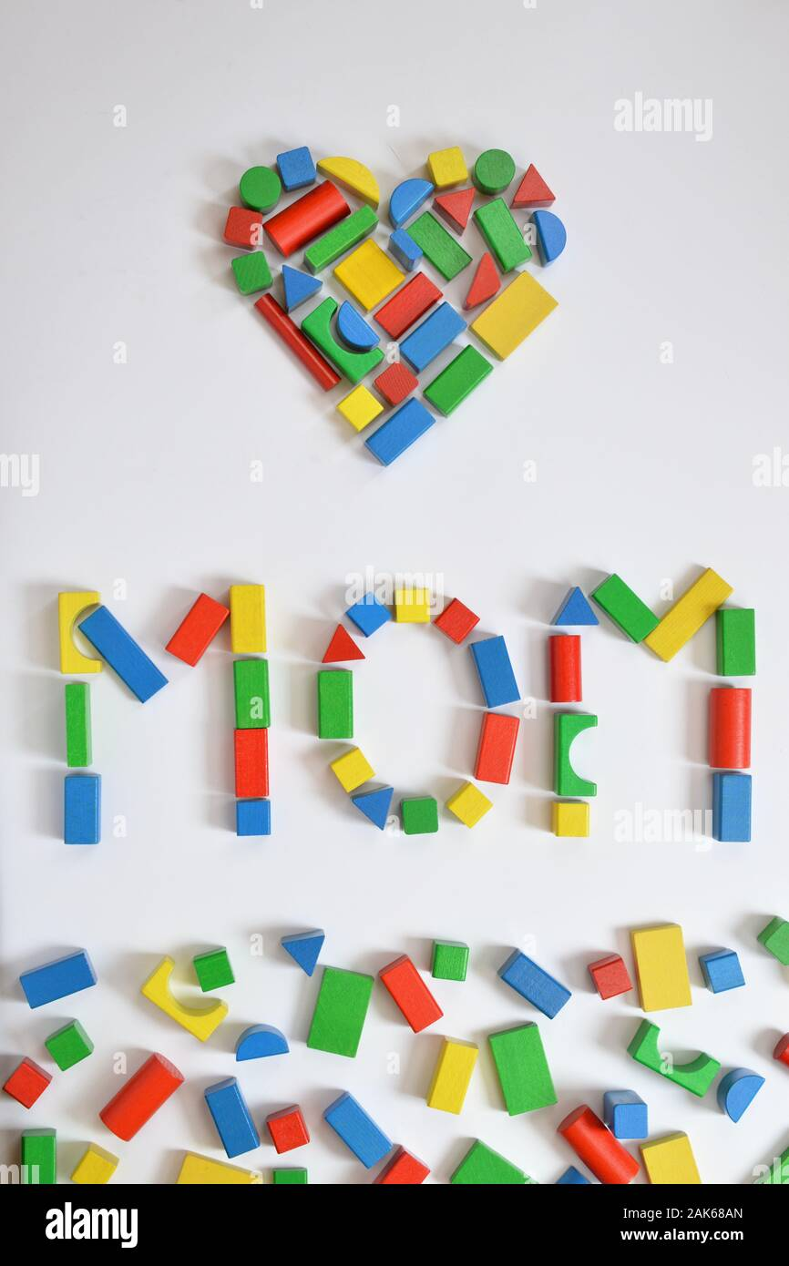 colorful wooden toy blocks lettering the word MOM and a heart on white background Stock Photo