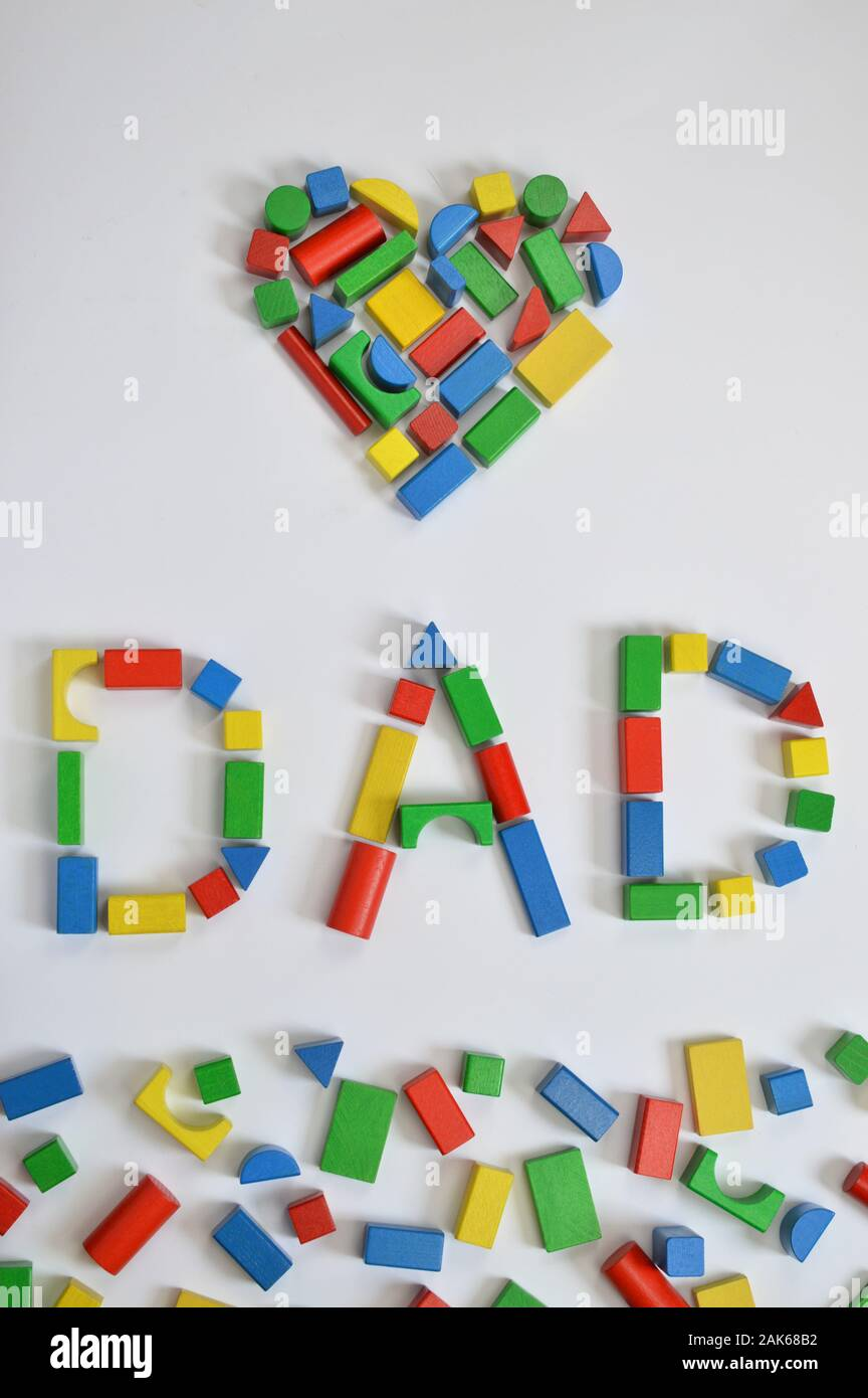 colorful wooden toy blocks lettering the word DAD and a heart on white background Stock Photo