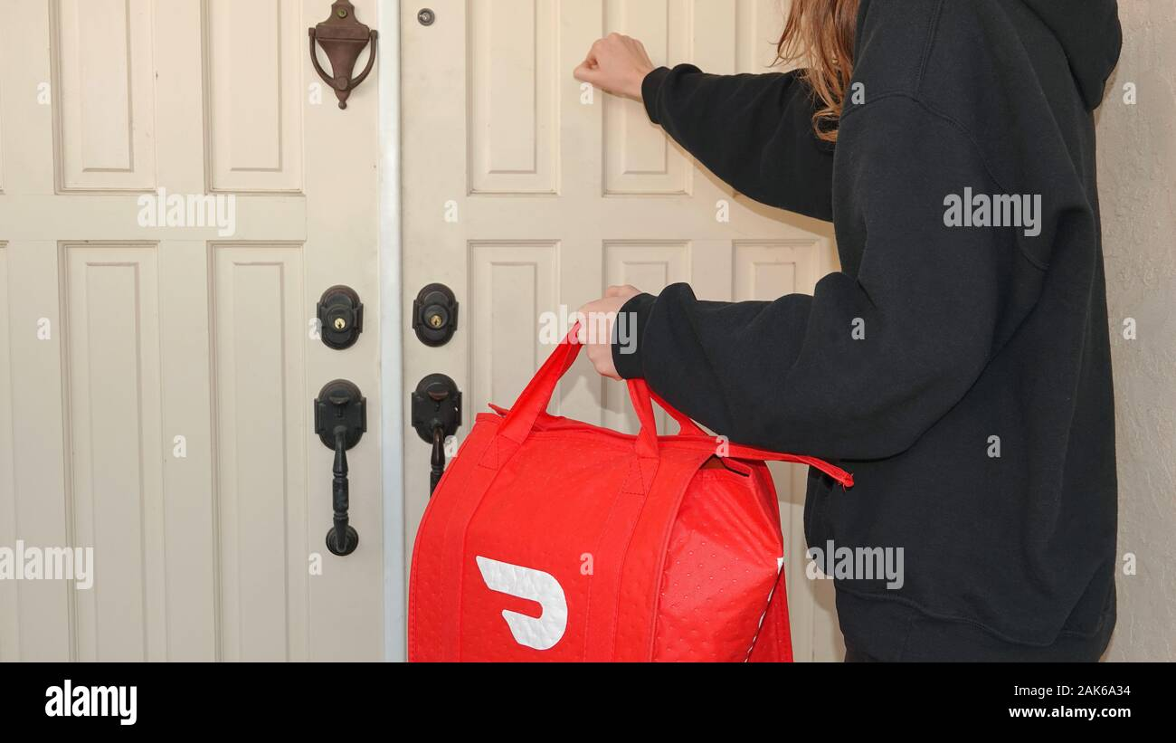 Person knocking on a door, making a DoorDash delivery. Stock Photo