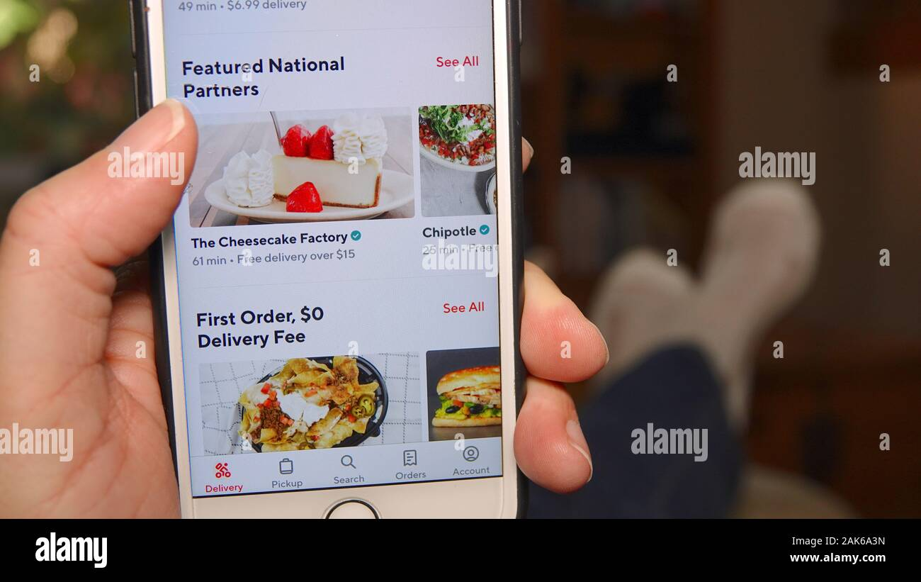 Person at home, using DoorDash app to order food. Close up of phone screen. Stock Photo