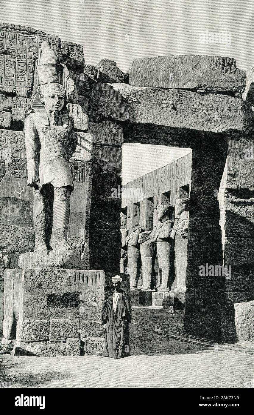 This illustration of the ruins of the Statue of Ramses II Iand his Temple at Karnak dates to the early 1900s. The nearly 200-foot-long temple features three chapels, a hypostyle hall with eight columns, a vestibule with four columns, and an open court. The court is surrounded by statues of Ramses III in his Jubilee vestments (can see in left background). A statue of Ramses stands by the entranceway here. Ramses III (died c.1155 B.C.) was the second Pharaoh of the Twentieth Dynasty in Ancient Egypt. Stock Photo