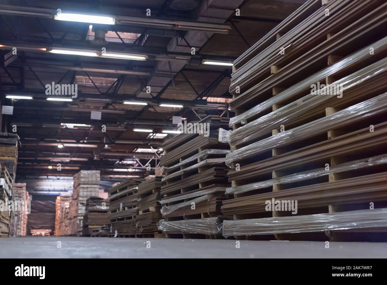 Timber Flooring Factory. Pile of cut wood in factory storage warehouse. Lumber in warehouse. Stock Photo