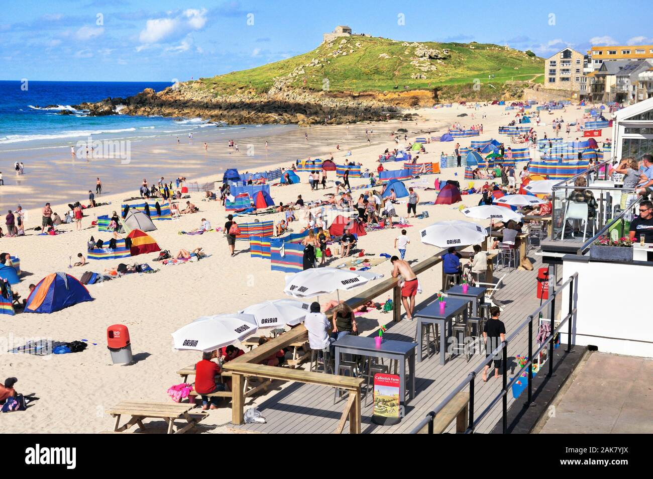 Holidaymakers enjoying the sun on Porthmeor beach in high summer at the popular seaside resort of St Ives in Cornwall, England, UK Stock Photo