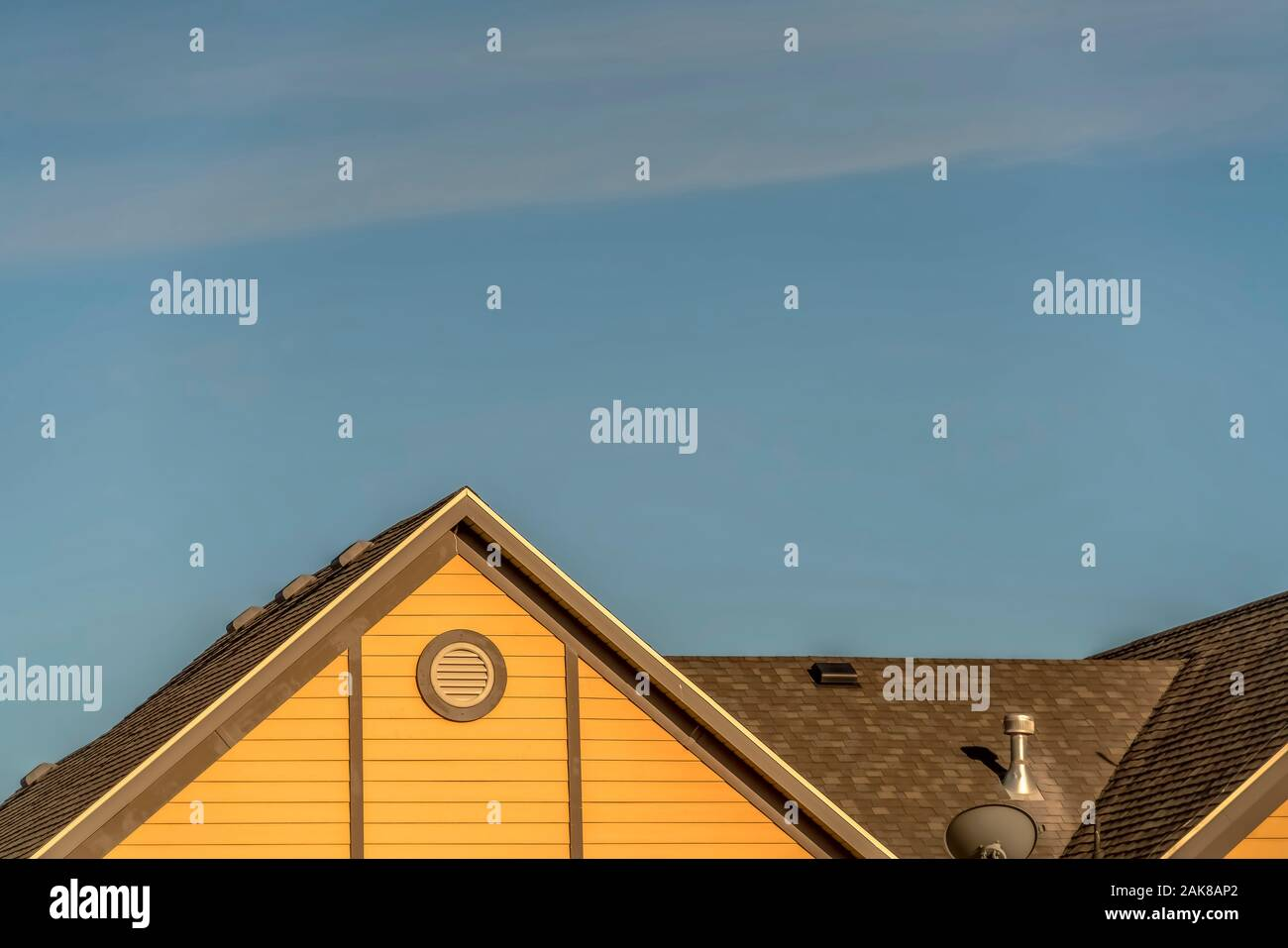 house exterior with roof shingles and round gable window against blue sky 2AK8AP2