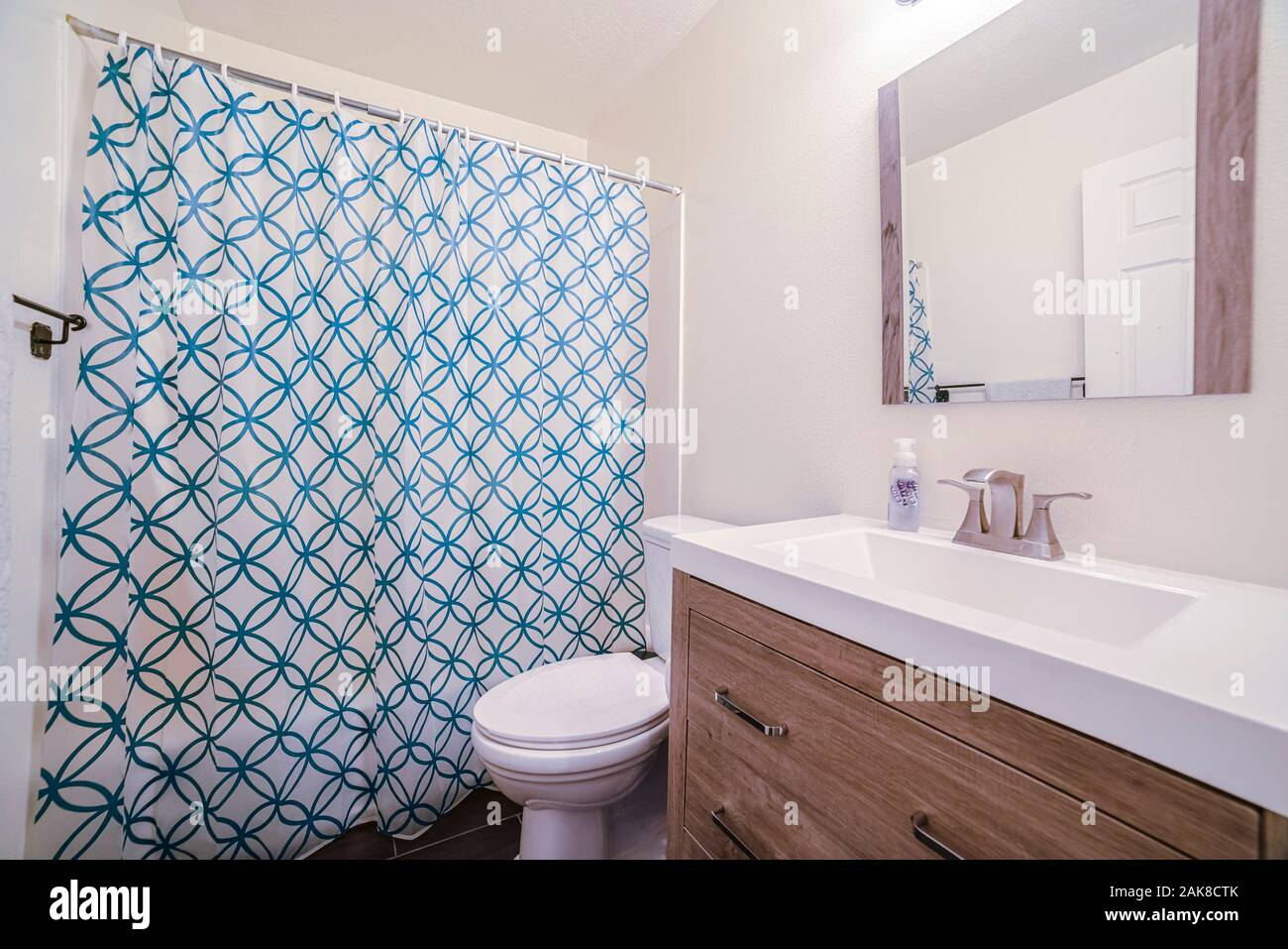 Small Bathroom With Patterned Shower Curtain In House Stock Photo Alamy